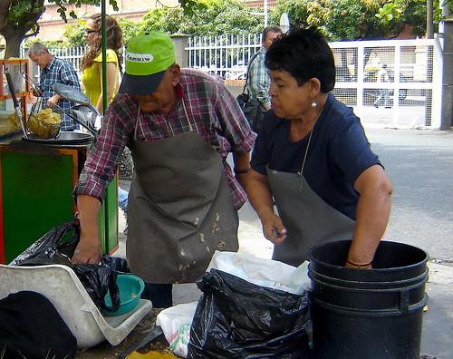 Socorro y Luis en su puesto de trabajo. En el balde negro ya están las papas negras sumergidas en agua limpia, mientras que las criollas reposan en la bolsa que está al pie del balde.