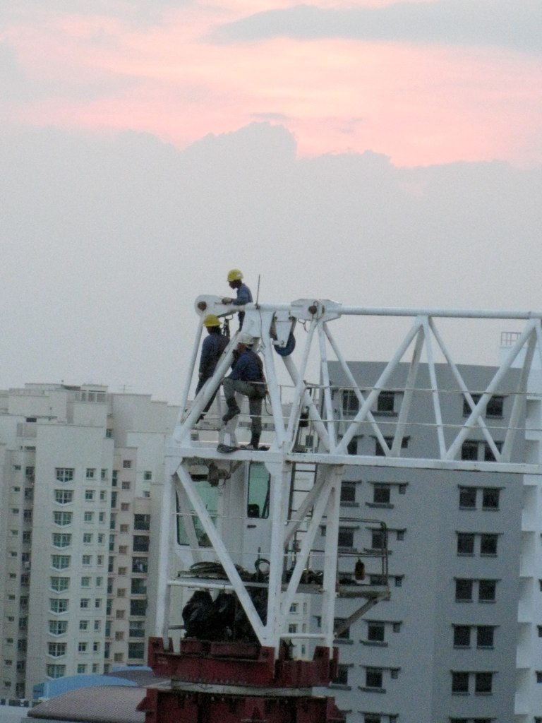 Workers securing parts of a crane