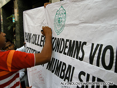 People signing a banner that condone violence