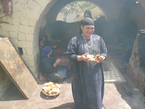 Women making bread (through the grill smoke)