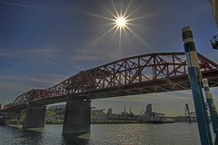 Broadway Bridge with Sun Flare - Portland Oregon - HDR (David Gn Photography) Tags: oregon portland landscape cityscape waterfront steel transportation pacificnorthwest conventioncenter pdx willametteriver hdr sunflare industrialarea broadwaybridge portlandbridges downtoan canoneos7d sigma1020mmf35exdchsm