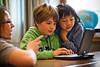 Grundschüler schauen gemeinsam auf das drehbare Display des Classmate PC