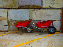 Red Greens (Steve Taylor (Photography)) Tags: wheelbarrow building wall red yellow grey block metal rust newzealand nz southisland canterbury christchurch diagonal lines two