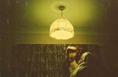 peering (Adele M. Reed) Tags: light selfportrait film girl bulb 35mm neck bedroom fuji shadows scan shade 200 curtains dust fingermarks nikonl35 adelemreedportfolio
