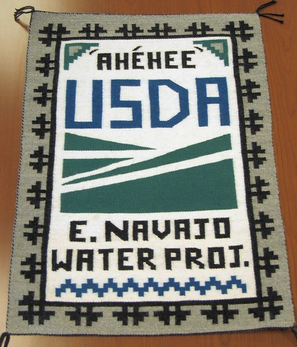 "A Navajo rug was presented to State Director Terry Brunner during the dedication and blessing of the Eastern Navajo Waterline ceremonies. The rug was crafted by a local artesian. The word ""Ahehee"" means """"Thank you"" in Navajo."