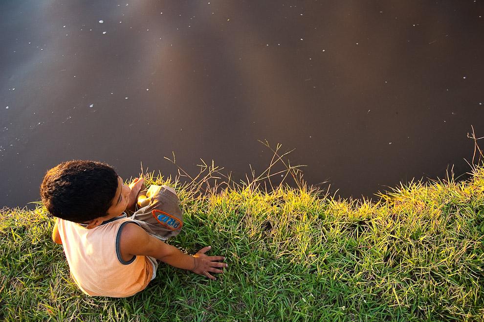 Un niño se sienta al borde del Río Jejuí mojando las puntas de sus pies el viernes santo, la subida del río debido a las continuadas lluvias de marzo elevaron la costa ocultando las playas de arena. (San Pedro, Paraguay - Elton Núñez)