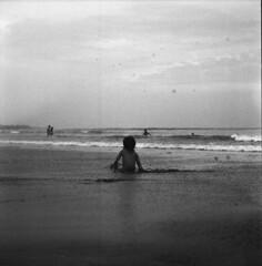 kid @ kuta beach (.a_dit.) Tags: sea bw bali cloud 120 mamiya film beach kid sitting child cloudy kodak trix sit medium format f28 kuta c22 80mm autaut aditmawar
