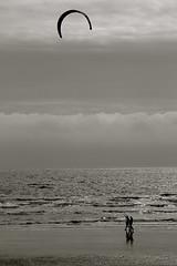 Extra Layers (nathanswan) Tags: sea england sky blackandwhite bw cloud sun white kite black beach water monochrome sussex seaside sand surf wind unitedkingdom britain candid cambersands wave monotone pebbles kitesurfing shore kitesurfers greyscale nathanswan