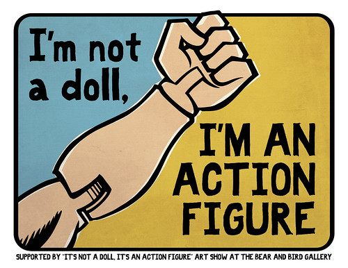 """I'm not a doll, I'm an ACTION FIGURE"" sign"