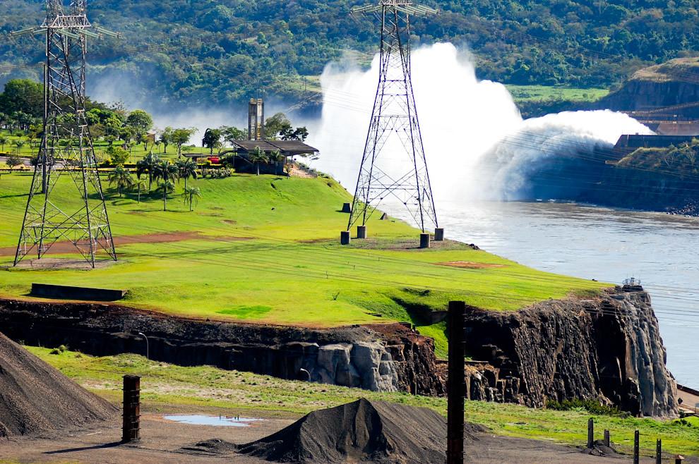 Vista desde el dique de la Represa Itaipú, del lado Brasilero se visualizan las oficinas y palcos de conferencias y presentaciones. A la derecha del lado Paraguayo una de la compuertas de alivio (drenaje) ofrece un lindo espectáculo visual. (Elton Núñez - Foz de Iguazú, Brasil)
