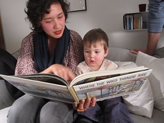storytime by grabadonut, on Flickr - image of an adult woman reading to a small child from a large book, pointing at something on the page