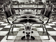 Strangely Seated in Symmetry (TheWalkinMan) Tags: bw restaurant blackwhite chairs symmetry tables mirrorimage checkerboard stainless southwedgediner