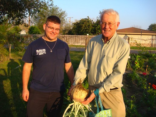 Dr. Alan Kirk (USDA-ARS) and a McAllen fireman admire a large turnip that was harvested from the garden.