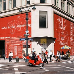 red vespa on 5th (ho_hokus) Tags: street nyc red newyork film 35mm vespa traffic manhattan transport 5thavenue scooter billboard midtown 35mmfilm motorcycle fifthavenue chinonbellami fujisuperiaxtra400