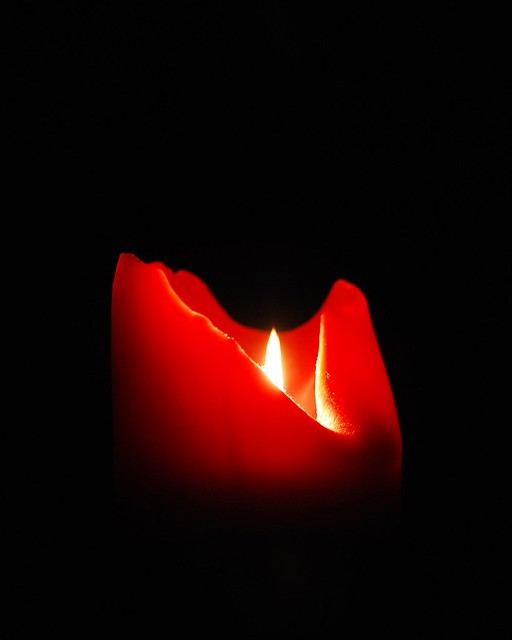 A red candle in darkness.