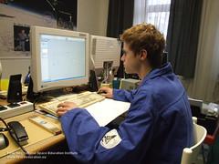 ein Jugendlicher, der in einem blauen Anzug, am Computer konstruiert.