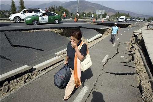 Una mujer camina junto a una carretera destruida tras el terremoto por Globovisión.