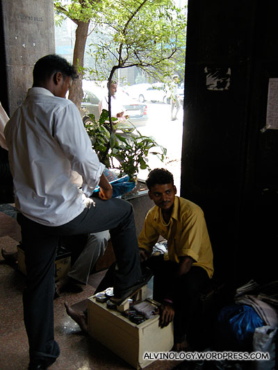 There were lots of shoe polishers like this chap here in the business district
