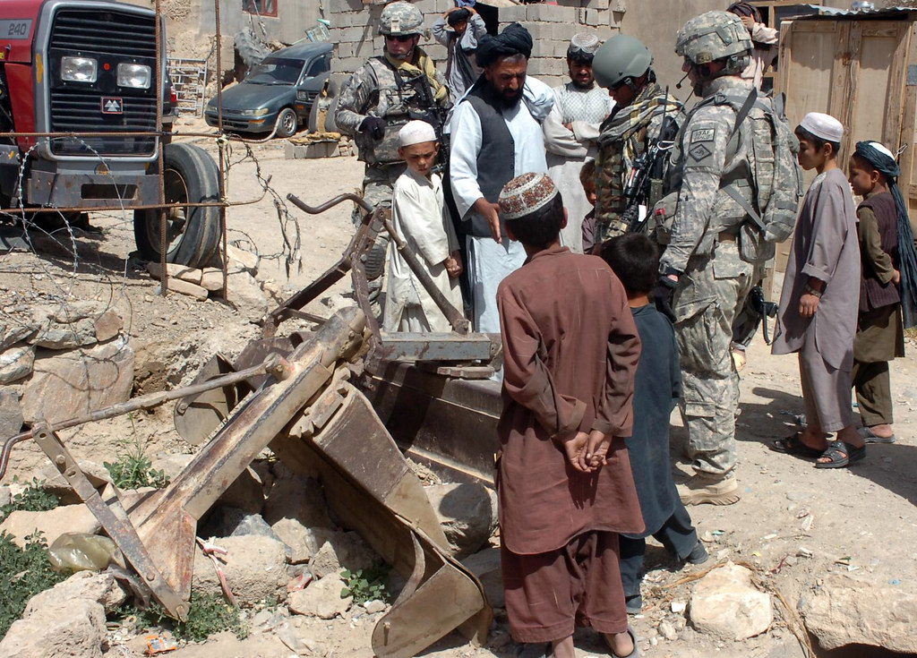 Arkansas Guardsman discusses farming equipment with a dealer in Afghanistan