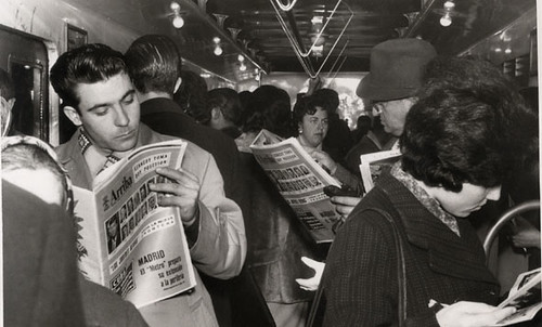 Black and white photograph of train travellers reading newspapers