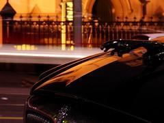 back to basics #2 (mugley) Tags: city longexposure urban orange black car night digital fence reflections fuji dof bokeh australia melbourne victoria doorway ornament finepix parked cbd lighttrails jaguar streaks bonnet s5500 digicam nocturne hoodornament obsolete 4megapixel urbanscene latrobest welshchurch fujifilmfinepixs5500 dinkycam akas5100