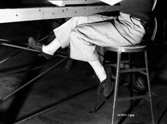Footwear worn by a woman munitions worker as she sits at a table in the John Ingl