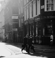 A step in time (Ian Brumpton) Tags: street blackandwhite bw london blancoynegro blackwhite couple noiretblanc candid citylife bodylanguage monotone explore shadowplay citystreets contrejour businessmen instep sidewalkstories explored londonstreetphotography humangeometry astepintime scattidistrada aimlessstrolling