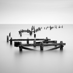 The Old Pier (Andy Brown (mrbuk1)) Tags: ocean wood longexposure sky seascape blur detail reflection texture broken water contrast square mono pier blackwhite ruins decay seagull horizon fineart minimal dorset highkey rotten curve posts ghostly swanage remains cliche timbers nd110 leefilters nd106