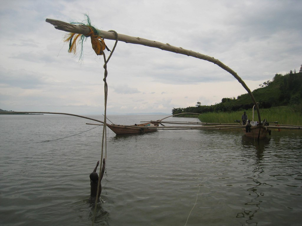A child reaches for ropes hanging from a traditional fishing boat.