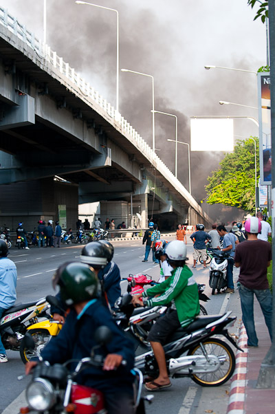 Locals look at burning tires on a bridge near Thanon Silom, Bangkok