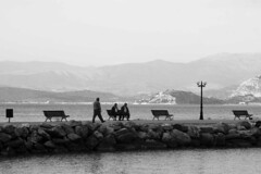 The stroll on the pier - May222010_0375ed (Dimitris Papazimouris) Tags: old bw men greek pier walk greece benches canon30d canon24105f4 kyveri