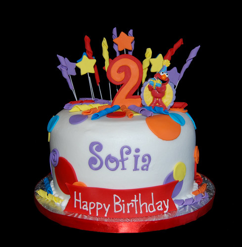 Red orange yellow blue and purple 2nd birthday cake with Elmo candle
