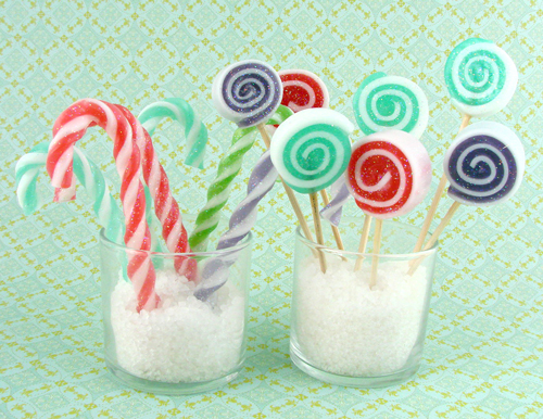 candy canes made of soap, standing in a cup, along with a cupful of spiral soap lollipops in various colours