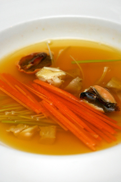Saffron infused mussel consomme with low temperature braised patte jaune chicken and spring vegetable julienne