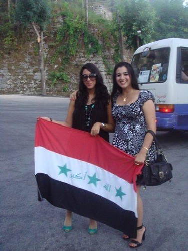 Beautiful Iraqi women in western dresses and sunglasses holding an Iraqi Flag
