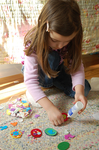 Assembling felt eggs with fabric glue.
