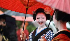 April Showers : The maiko (apprentice geisha) Mamehana (momoyama) Tags: city travel friends red portrait people woman flower colour girl beautiful beauty smile rain japan umbrella canon japanese spring kyoto couple asia traditional culture 85mm explore maiko geisha 7d laugh   kimono ef85mmf18  mamehana
