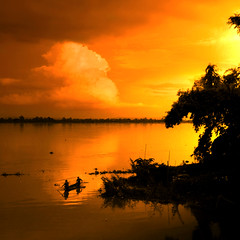 Sunset over the Mekong River (Bn) Tags: sunset night fishing fisherman topf50 cloudy topf300 brightcolors laos topf100 500faves topf200 mekong vividcolors champassak topf400 topf500 southernlaos champasak orangesunset sunsetcolors fishersboat magiccolors stunningcolors topf600 100faves goldenmome