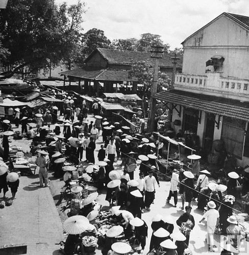 1948 - Vendors selling their wares in busy marketplace.