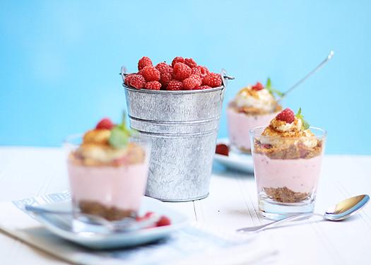 No Bake Raspberry Cheesecake Pots surrounding a bucket of raspberries