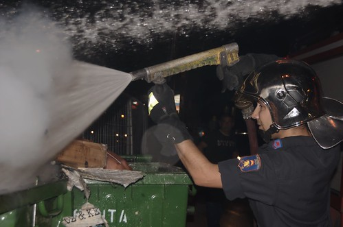 Fireman extinguishes trash cans set ablaze by football fans