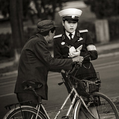 Trafic officer and biker - Pyongyang North Korea (Eric Lafforgue) Tags: street people blackandwhite woman man male bike bicycle female square person war uniform asia noiretblanc femme capital fine police korea communism gloves biker asie capitale dailylife distrust rue coree suspicion velo personne humanbeing communisme homme northkorea cycliste uniforme pyongyang dprk coreadelnorte carre gants nordkorea blackandwhitepicture waistup squarepicture 8453 democraticpeoplesrepublicofkorea    coreadelnord amnde  etrehumain coreedunord  insidenorthkorea  rpdc  kimjongun coreiadonorte  republiquepopulairedemocratiquedecoree cadragealataille imagecaree