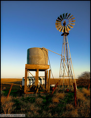 Zamora Windmill (nosniv) Tags: ranch blue sunset windmill grass northerncalifornia fence weeds farm horizon tires pastoral barbwire watertank zamora goldenhour sacramentovalley i505
