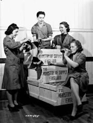Group of female workers enjoying a break from their work of packing crates of 25-pounder field gun cases at a munitions plant (prob. Robert Mitchell Co.) / Dans une fabrique de munitions, un groupe d'ouvrires charges d'emballer des douilles d'obus pour (BiblioArchives / LibraryArchives) Tags: canada workers break montral quebec montreal wwii lac canadian worldwarii qubec pause canadians canadiens 1941 canadien bac secondworldwar canadienne femal ouvrires libraryandarchivescanada canadiennes deuximeguerremondiale bibliothqueetarchivescanada nicholasmorant 25pounderfieldguncases obuspourcanonsde25livres