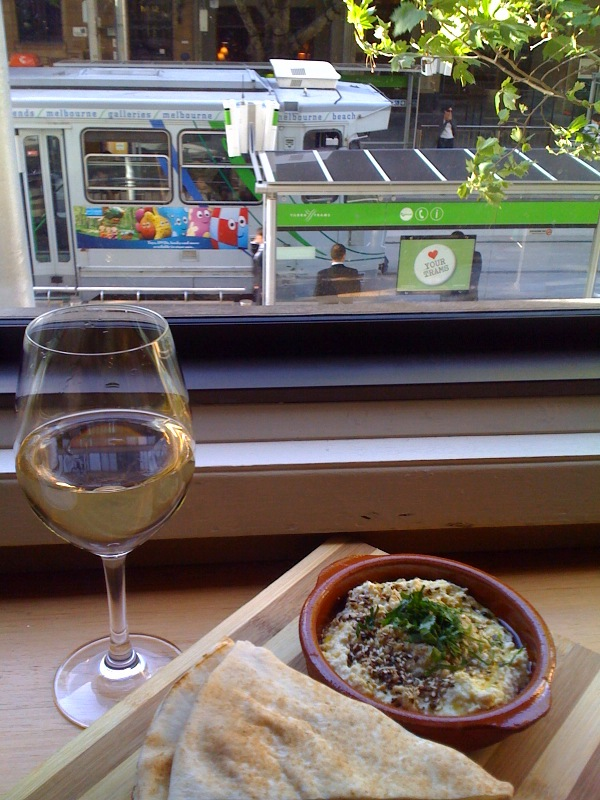 Relaxing with a glass of white and delicious nosh, watching the world below go by.