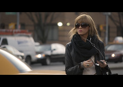 the style of the city. (Vitaliy P.) Tags: nikon d80 project365 project 365 month12 year2 55200mm vr candid street photography cinematic movie film crop black bars wide girl young woman walking scarf ipod huge sunglasses attitude mean lipstick lip gloss yellow taxi cab vitaliyp lower east side manhattan new york city nyc