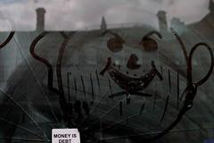 Money Is Debt (bandashing) Tags: england reflection abandoned window shop dark manchester grey smash sticker sinister empty evil crack reflect vandalism damage draw smashed sylhet bangladesh cracked bandashing