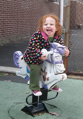 little girl in colorful dotted coat makes a wild face on hobby horseback