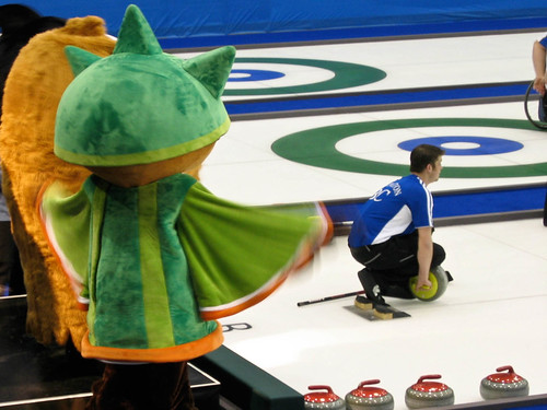 Mascots at ice level watching curling