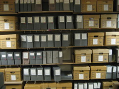 Archival boxes of varying sizes on a range of shelves